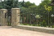 Kovane ograje med betonskimi stebri